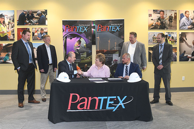 Kelly Delgado-Goudschaal (c), Pantex supply chain manager, signs the first Consolidated Nuclear Security, LLC Mentor-Protégé agreement at Pantex with brothers Samuel and Saul Maldonado, Chief Executive Officer and President respectively of SAM Engineering & Surveying, Inc.